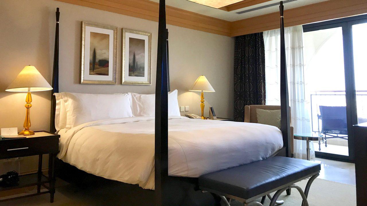 Luxushotel The Ritz-Carlton Abu Dhabi großes Doppelbett in der Royal Suite. Goldene Lampen, weiße Bettwäsche, Zimmerblick zum Balkon