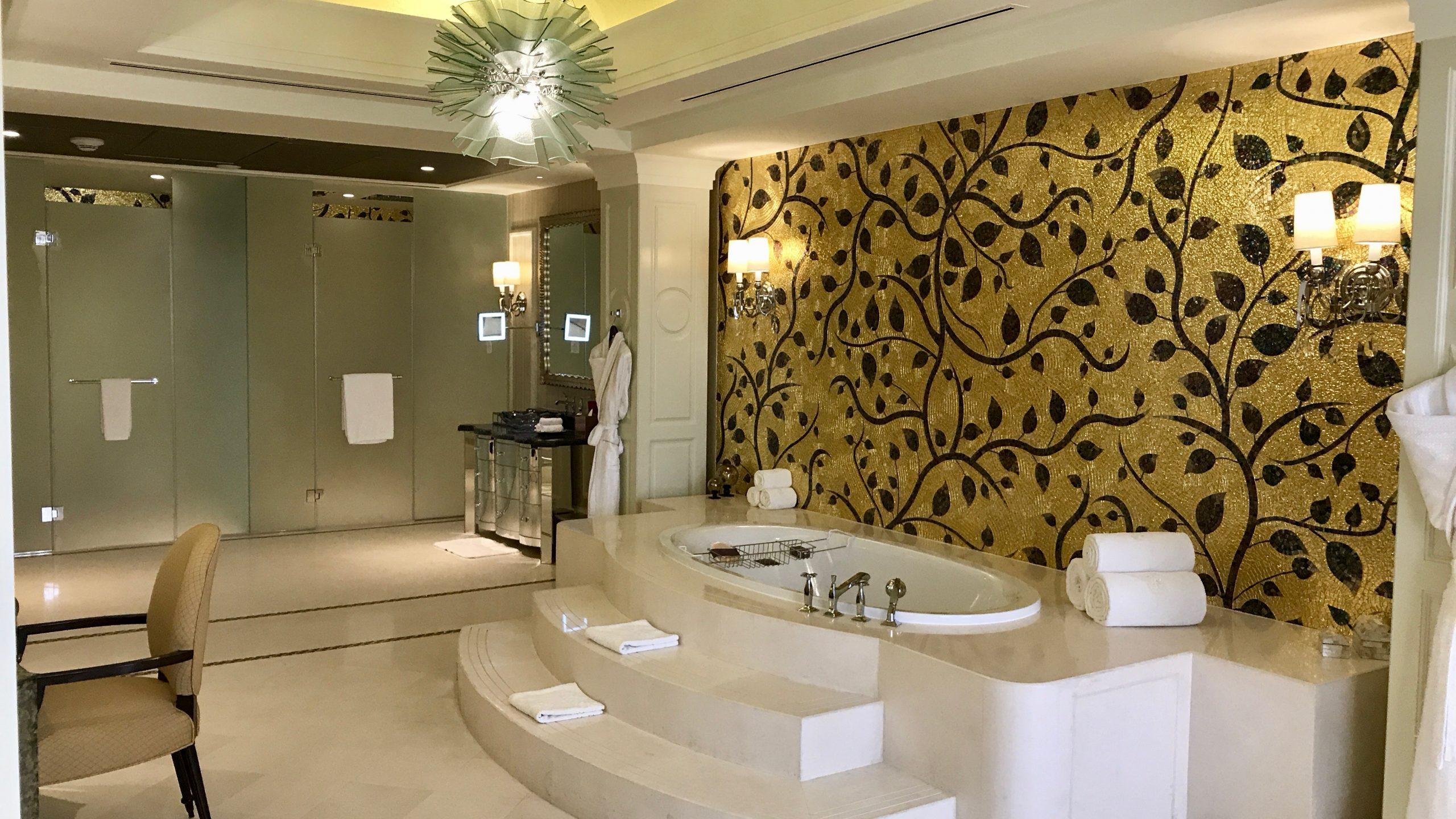 Luxushotel The Ritz-Carlton Abu Dhabi großzügiges Badezimmer in der Royal Suite. Goldene Wand, riesige Badewanne, Lampen und größter Luxus.
