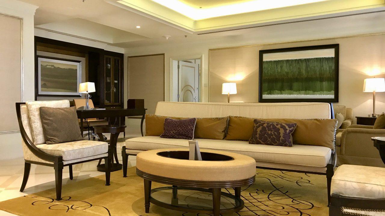 Luxushotel The Ritz-Carlton Abu Dhabi großzügige Royal Suite. Wohnzimmer in goldenen Tönen mit Sofa, Kissen, Lampen, Sessel und Tisch. Sehr gediegen.