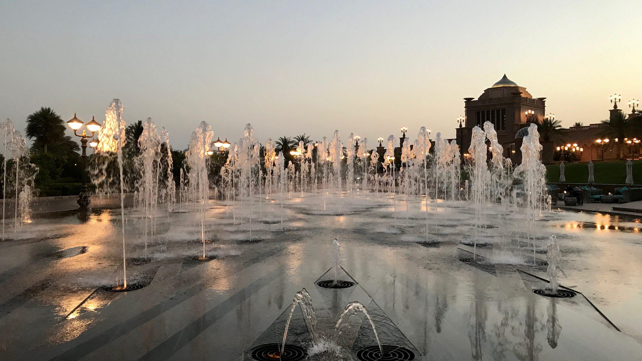 Wasserspiele beim Sonnenuntergang. Im Hintergrund sind die vielen Lampen und ein Teil der Außenfassade vom Luxushotel Emirates Palace in Abu Dhabi bereits erleuchtet. Lichter spiegeln sich im Wasser.