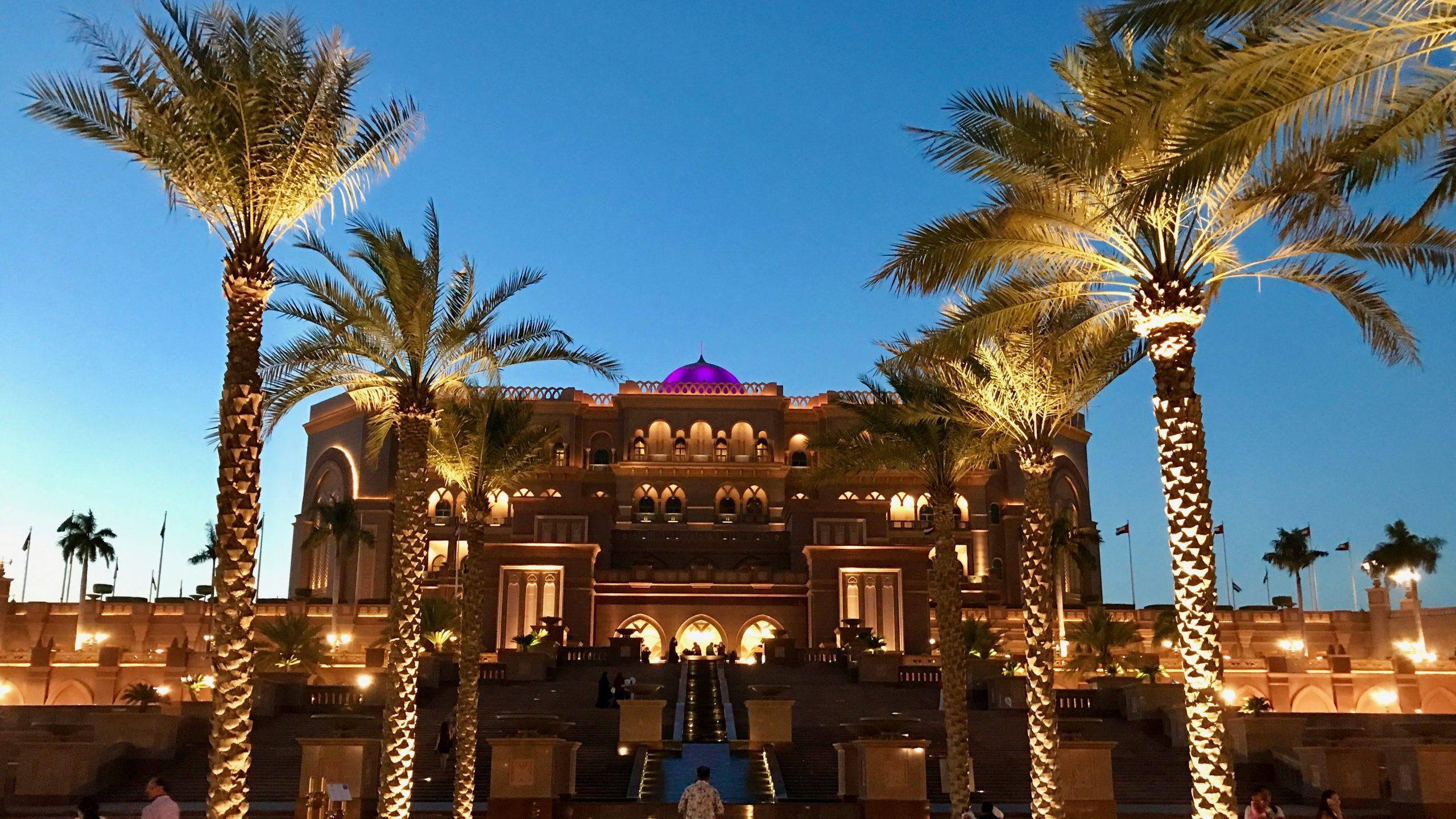 Einmalige Opulenz und ein Palast wie aus einem Märchen, das Luxushotel Emirates Palace in Abu Dhabi. Außenfassade überdimensional groß, von Palmen gesäumte Stufen zum Eingang. Blauer Nachthimmel wird von einem Lichtermeer zum Leuchten gebracht.