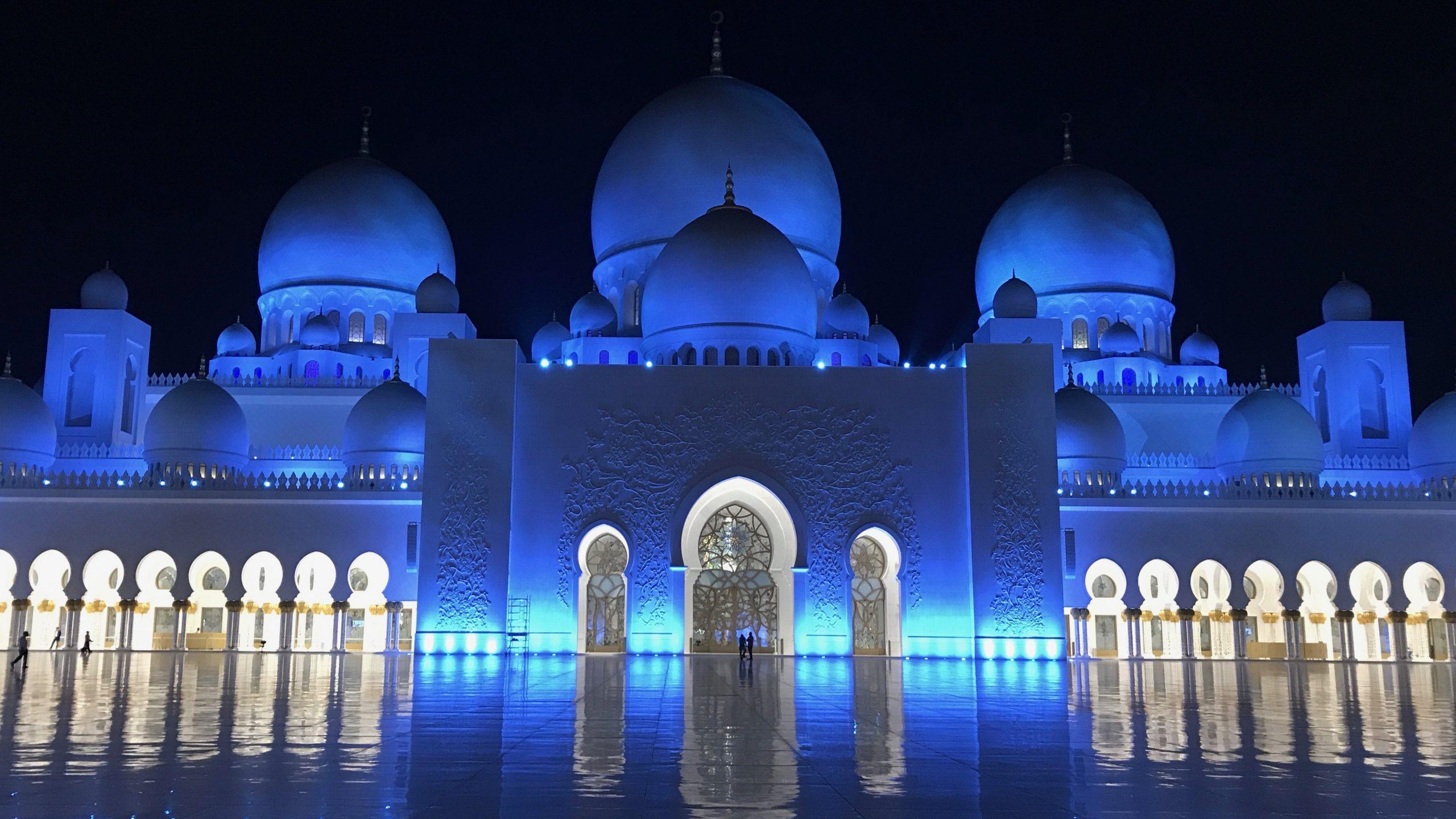Scheich-Zayid-Moschee Abu Dhabi bei Nacht. Blau leuchtet die Mosche und glänzt vor dem dunklen Himmel besonders schön. Der Marmorboden sieht dabei aus wie ein endloses Meer.