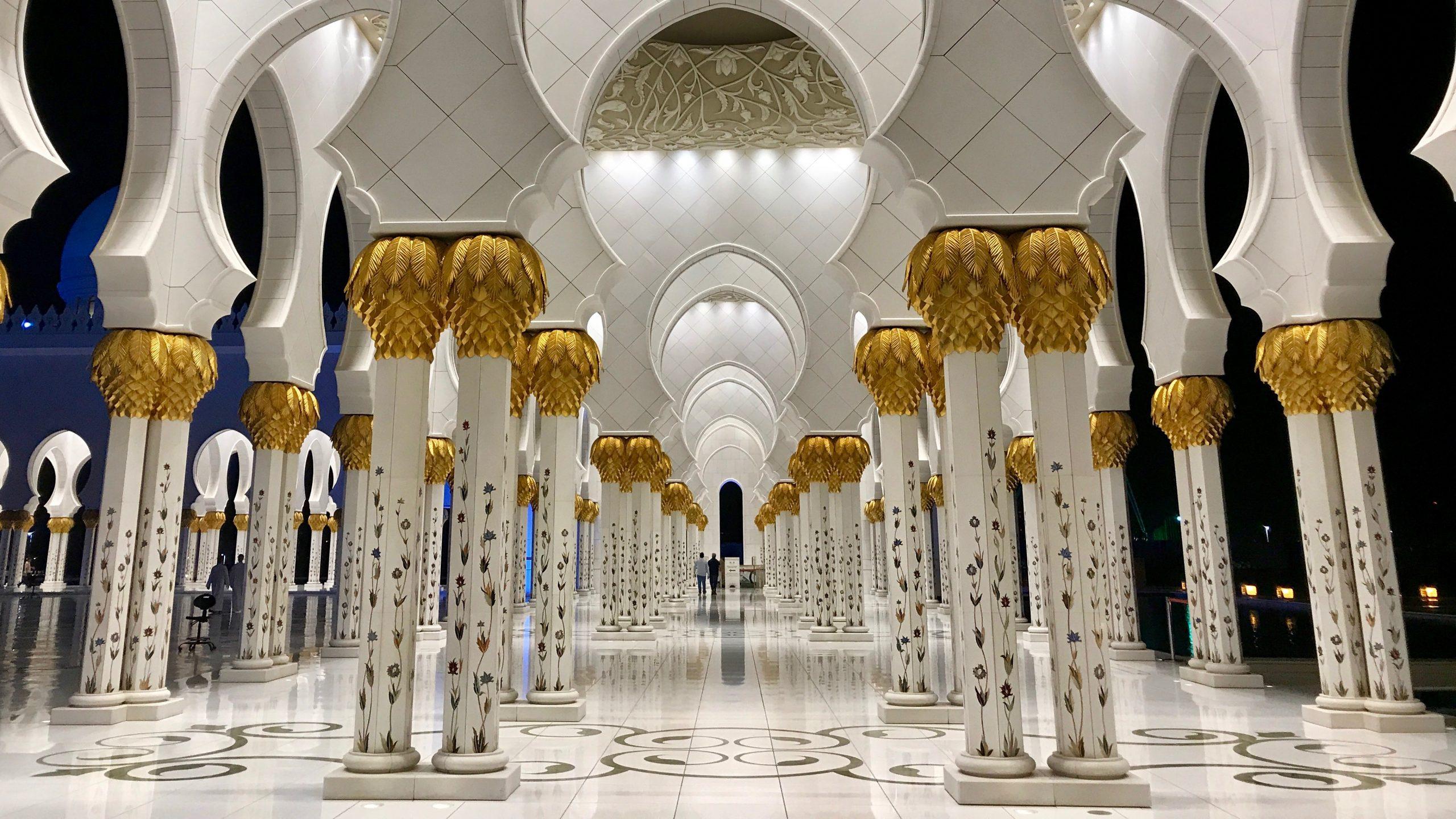 Scheich-Zayid-Moschee Abu Dhabi bei Nacht. Innen leuchtet die Mosche in hellem Kunstlicht. Das Gold der weißen Säulen glänzt vor dem dunklen Himmel. Der weiße Marmorboden strahlt und glänzt.