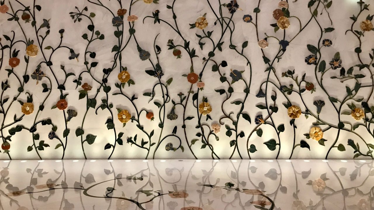 Wie ein Gemälde ranken bezaubernde gelb und orangene Blumen eine weiße Wand hoch. Die kunstvolle Handarbeit in XXL Dimension im Innenraum der Scheich-Zayid-Moschee spiegelt sich im hellen Marmorboden.