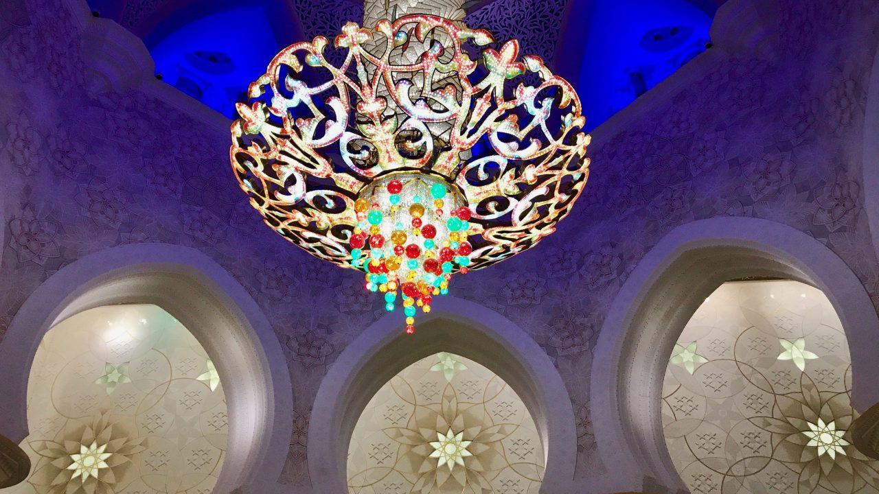 Von der Decke im Innenraum der Scheich-Zayid-Moschee hängt ein Kronleuchter in Regenbogenfarben, ein Prachtexemplar in XXL Größe. Die weißen Wände und Bögen drumherum sind mit wunderschönen kunstvollen Motiven verziert.