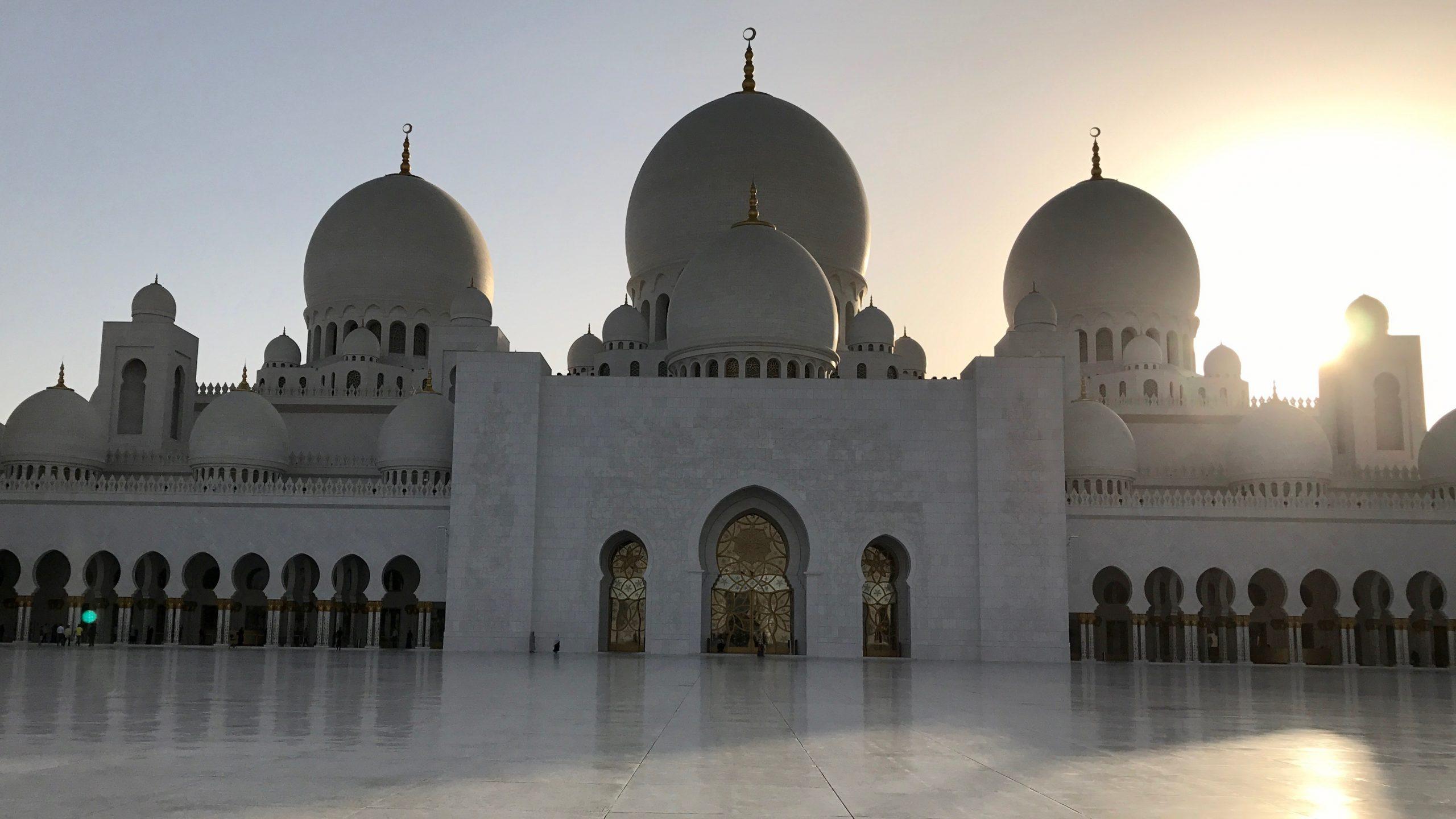 Scheich-Zayid-Moschee in Abu Dhabi beim Sonnenuntergang. Die weiße Außenfassade ist leicht im Schatten, wunderschöne Schattenspiegelungen sendet die untergehende goldgelbe Sonne auf dem blitzblanken Marmorboden.