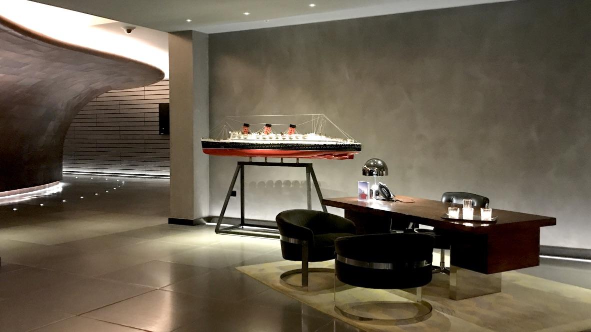 Hotel Mondrian Lobby im Style eines Kreuzfahrtschiffs. Links neben dem Tisch vom Concierge befindet sich ein dekoratives großes Queen Mary Schiff.