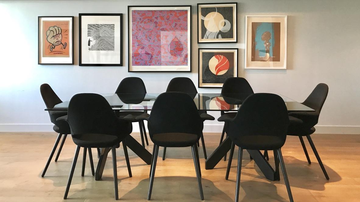 Hotel Mondrian River View Balcony Suite. Am dunklen Designer Tisch mit schwarzen Stühlen können 8 Personen Platz nehmen. Die Wand ist mit unzähligen Kunstwerken bebildert.