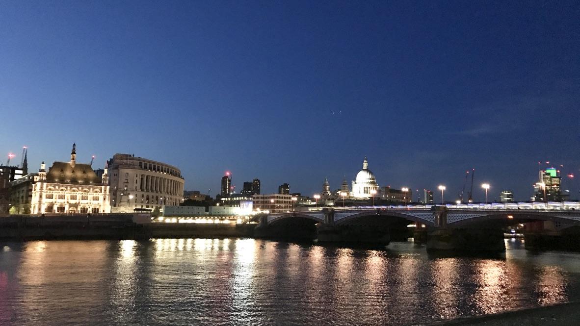London am Ufer der Themse bei Nacht. Unter dem nachtblauen Himmel von unzähligen Lichtern leuchtet die Stadt im Spiegel der Themse und gibt einen wundervollen Blick auf die St. Pauls Kathedrale frei.