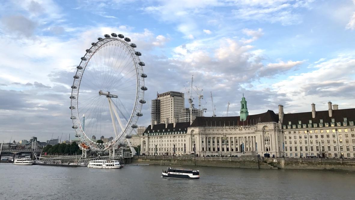 London Eye in voller Bildpracht. Dahinter ein blauer mit weißen Wolken durchsetzter Himmel. Mehrere Schiffe fahren die Themse entlang.
