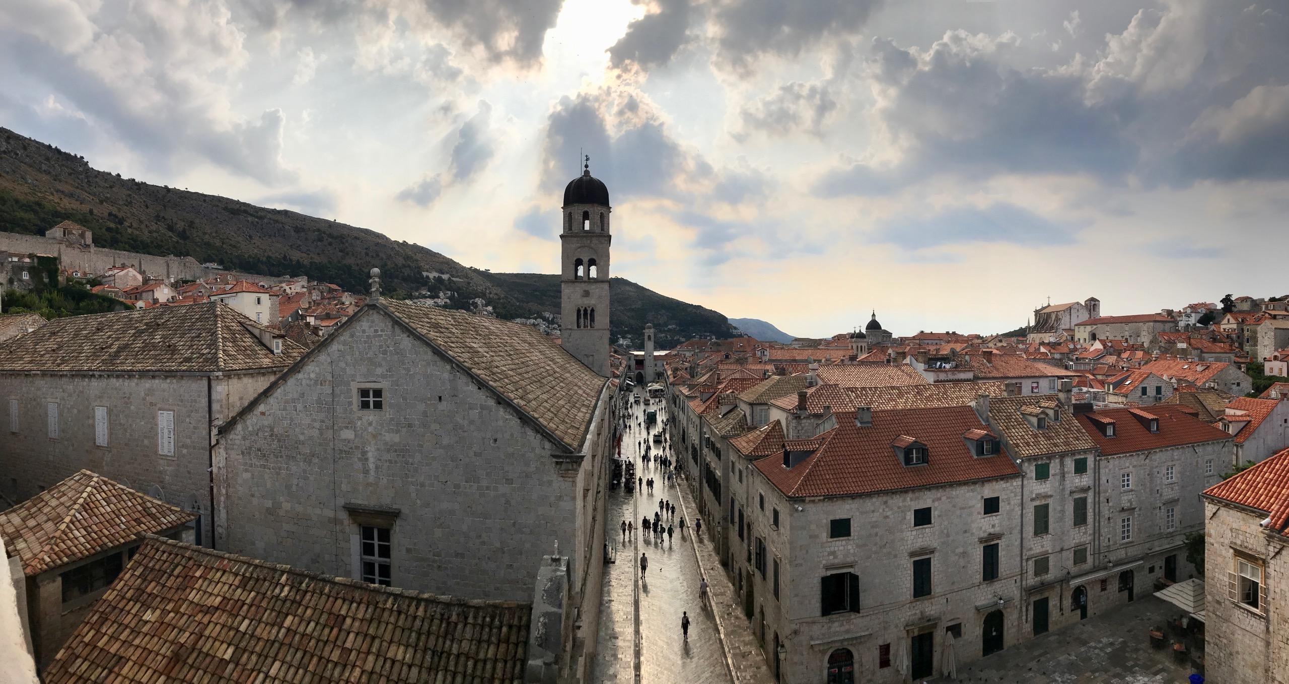 Dubrovnik Altstadt links und rechts die mittelalterlichen Häuser in der Mitte die Promenade. Am frühen Morgen sind nur wenige Menschen unterwegs, die Wolken werfen ein mystisches Bild auf die Altstadt