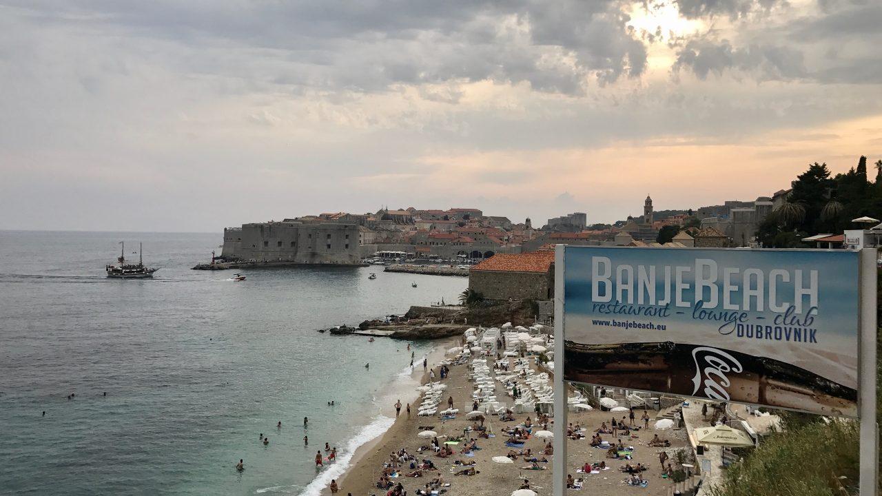 Vom Strand hast du den schönsten Blick auf Dubrovnik Altstadt. Sonnenhungrige genießen unter aufgespannten Sonnenschirmen und Sonnenliegen das türkisblaue Meer und den Blick auf die Altstadt