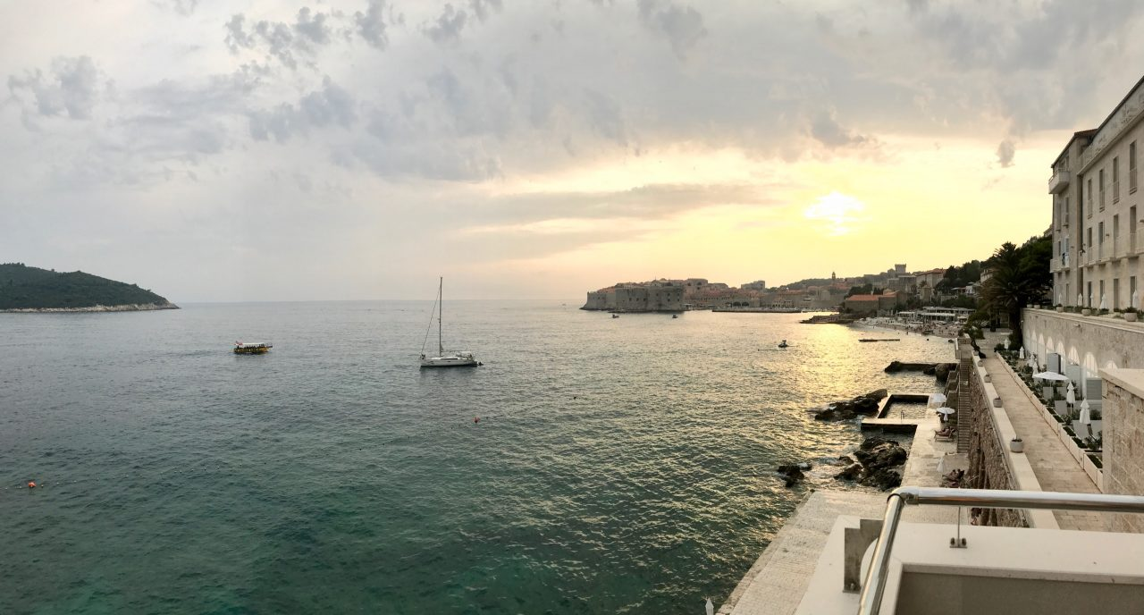 Blick von der Restaurant Terrasse, das aquamarinblaue Meer und die Altstadt von Dubrovnik im Sonnenuntergang, Segelbote vor der filmreifen Kulisse