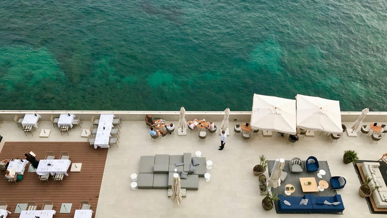 Ein Blick von oben auf die Restaurant Terrasse, die Bar und das aquamarinblaue Meer. Liegen Tische und Sessel laden zum chillen ein