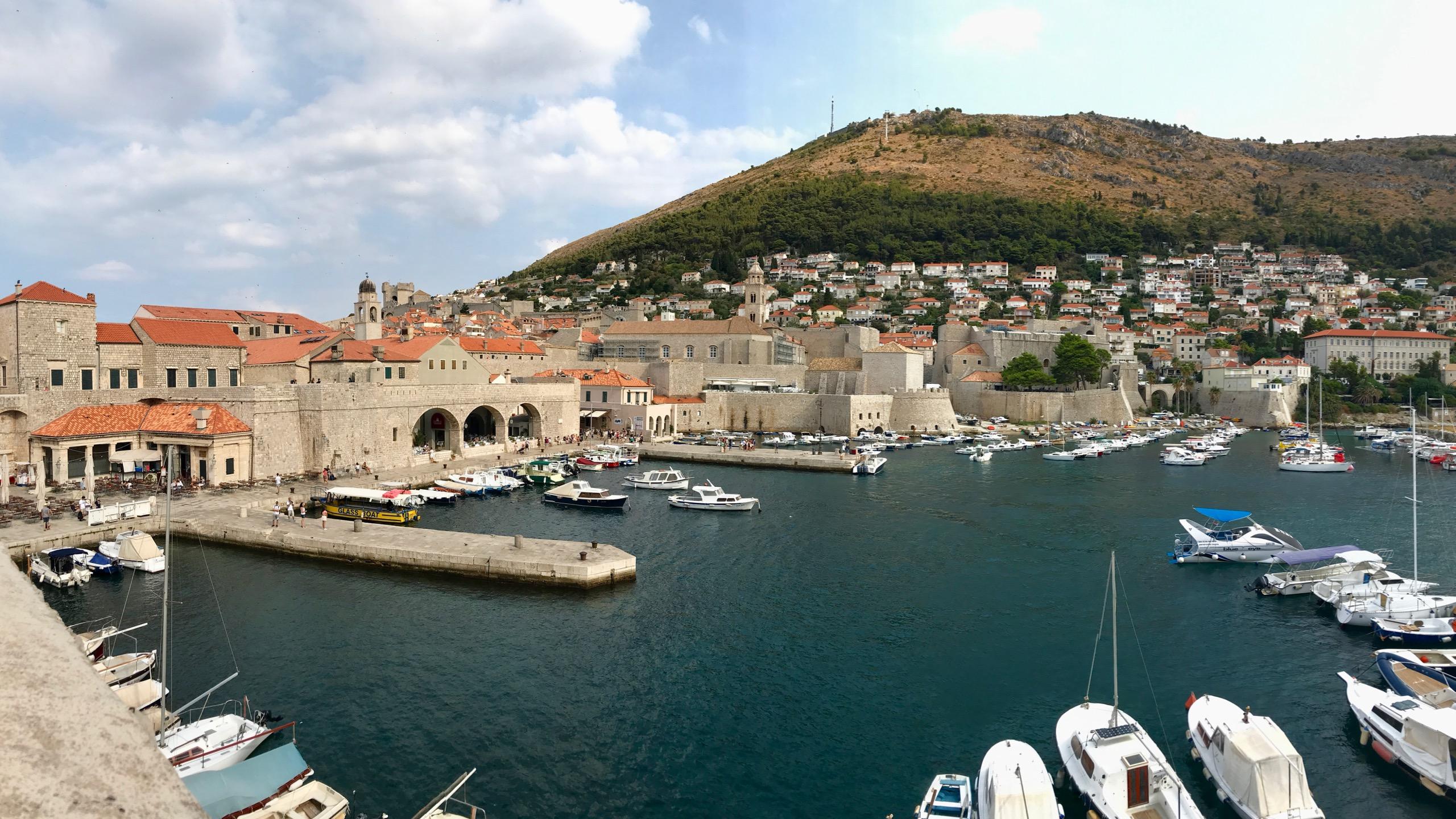 Dubrovnik Altstadt mit Blick auf den Hafen, viele Boote ruhen auf dem sanften türkisblauen Meer