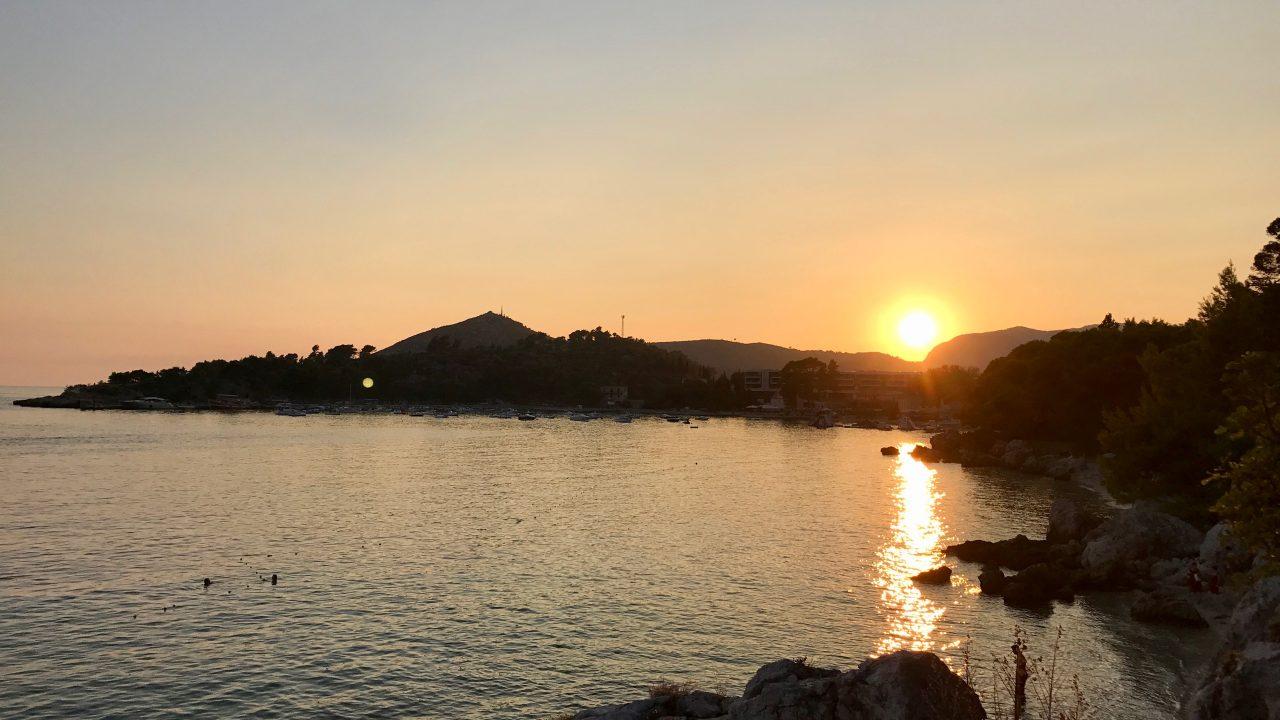 Am Strand beim Sonnenuntergang. Die untergehende goldene Sonne leuchtet im Meer. Wundervoller Blick auf die grüne und üppige Küste Kroatiens