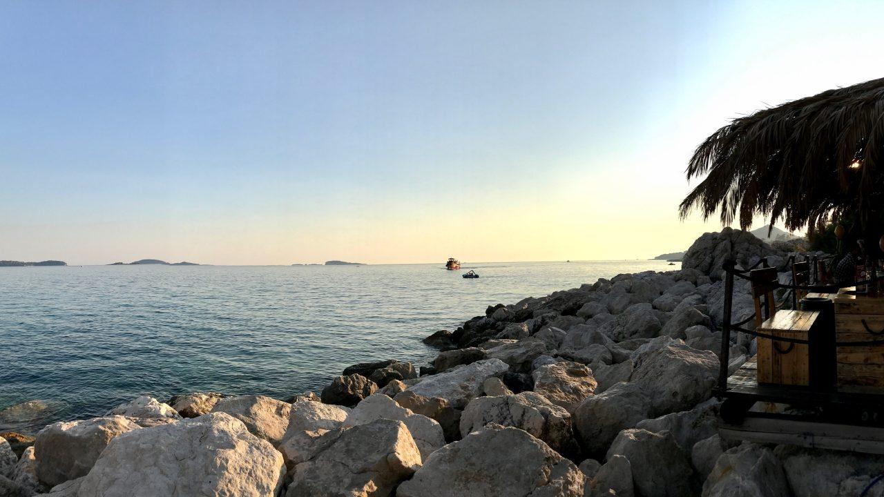 Sonnenuntergang in Kroatien am Meer mit Felsen und Beachbar