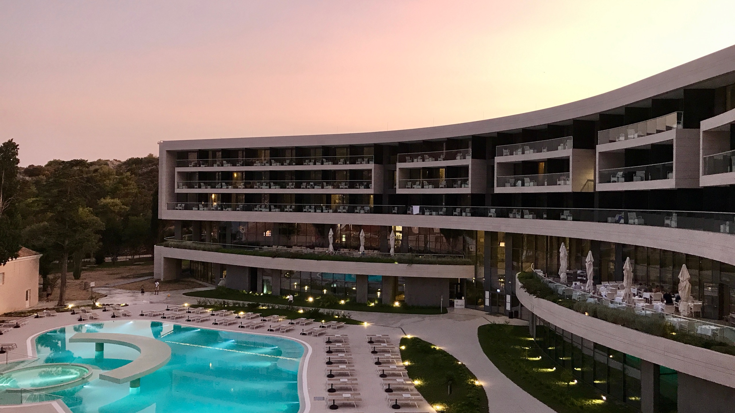 Dubrovnik Sheraton Hotel im rotgelben Sonnenuntergang, Pool ist türkis beleuchtet
