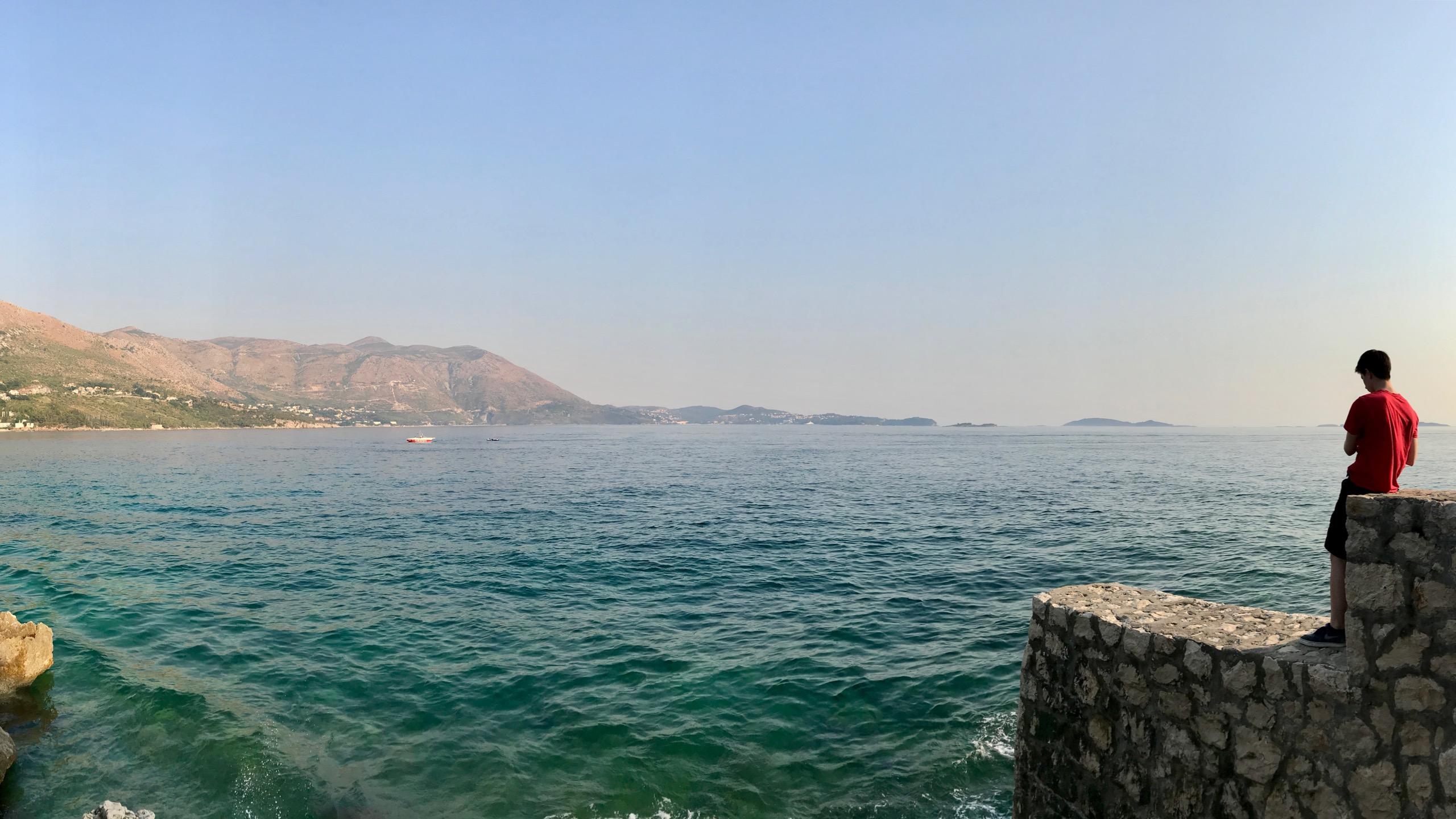 Türkisblaues Meer, im Hintergrund kahle Berge und grüne Natur. Ein Kind blickt auf das offene Meer hinaus
