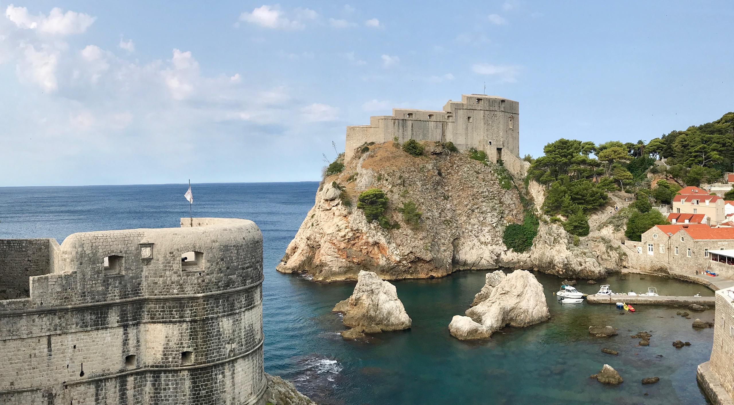 Blick von der Dubrovnik Stadtmauer auf die Festung Festung Lovrijenac. Ein sonnenbestrahlter Fels und drumherum das Meer