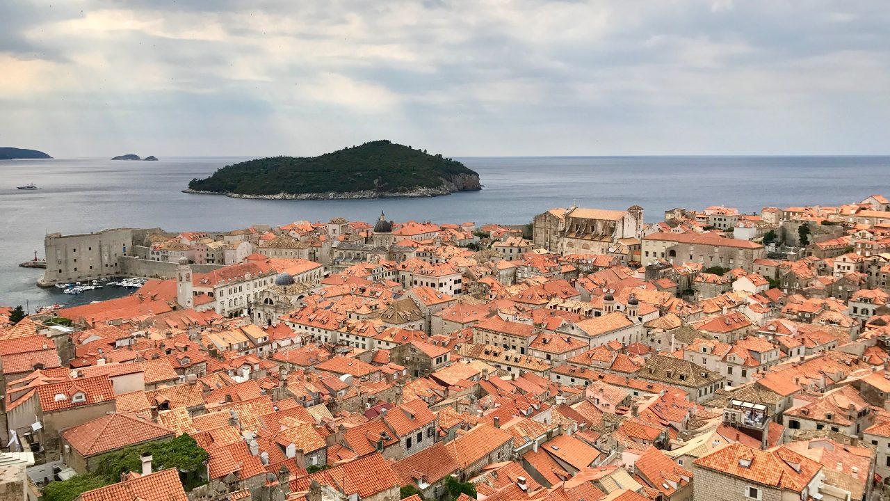 Dubrovnik Altstadt aus der Vogelperspektive, im Bild der Blick auf die Altstadt und die mittelalterliche Mauer, die roten Dachziegeln im Sonnenschein und die blaue Adria
