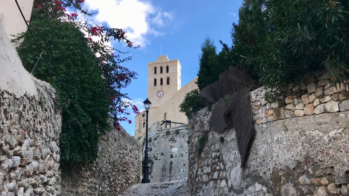 Ibiza Altstadt mit schmalen steilen Gassen und einer Kirche die in den blauen Himmel steigt.