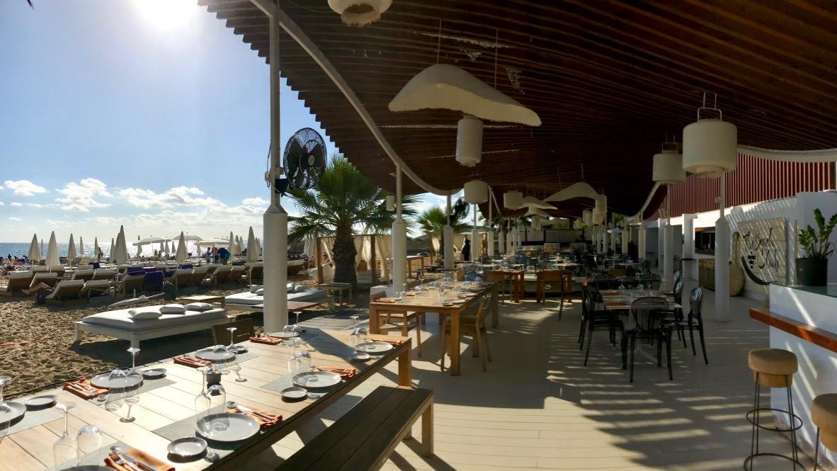 Hard Rock Hotel Ibiza der Beach Club. Weiße Liegen, Sonnenschirme, lange Tische, grüne Palmen und dahinter das blaue Meer. Traumhaft schön