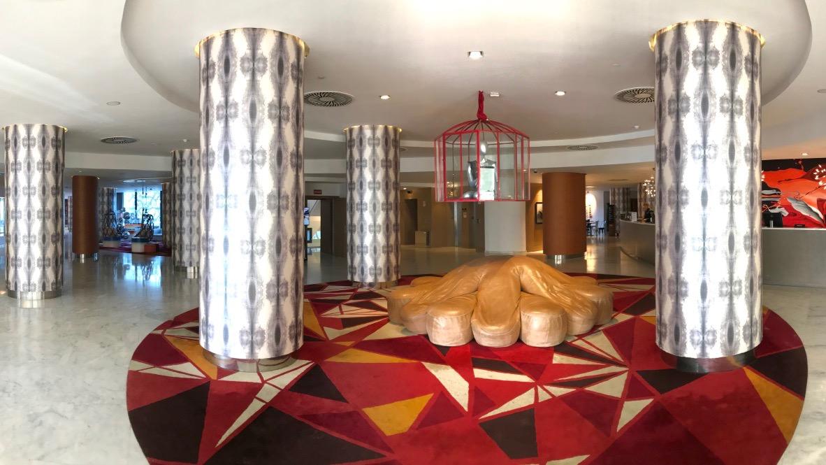 Hard Rock Hotel Ibiza, eine Lobby mit großen Säulen, bunten Teppichen und Sammlerstücken der Stars