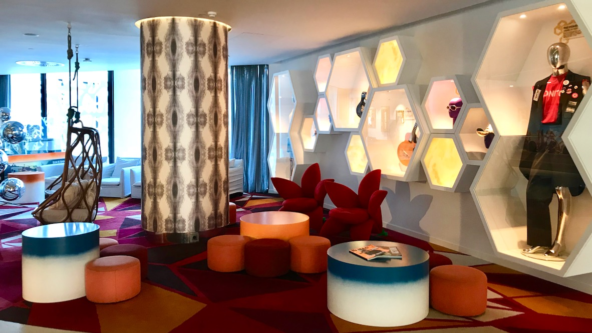 Hard Rock Hotel Ibiza, Lobby zum Chillen mit gemütlichen bunten Sofas, bunten Hockern, Tischen und Sammlerkostümen von berühmten Stars