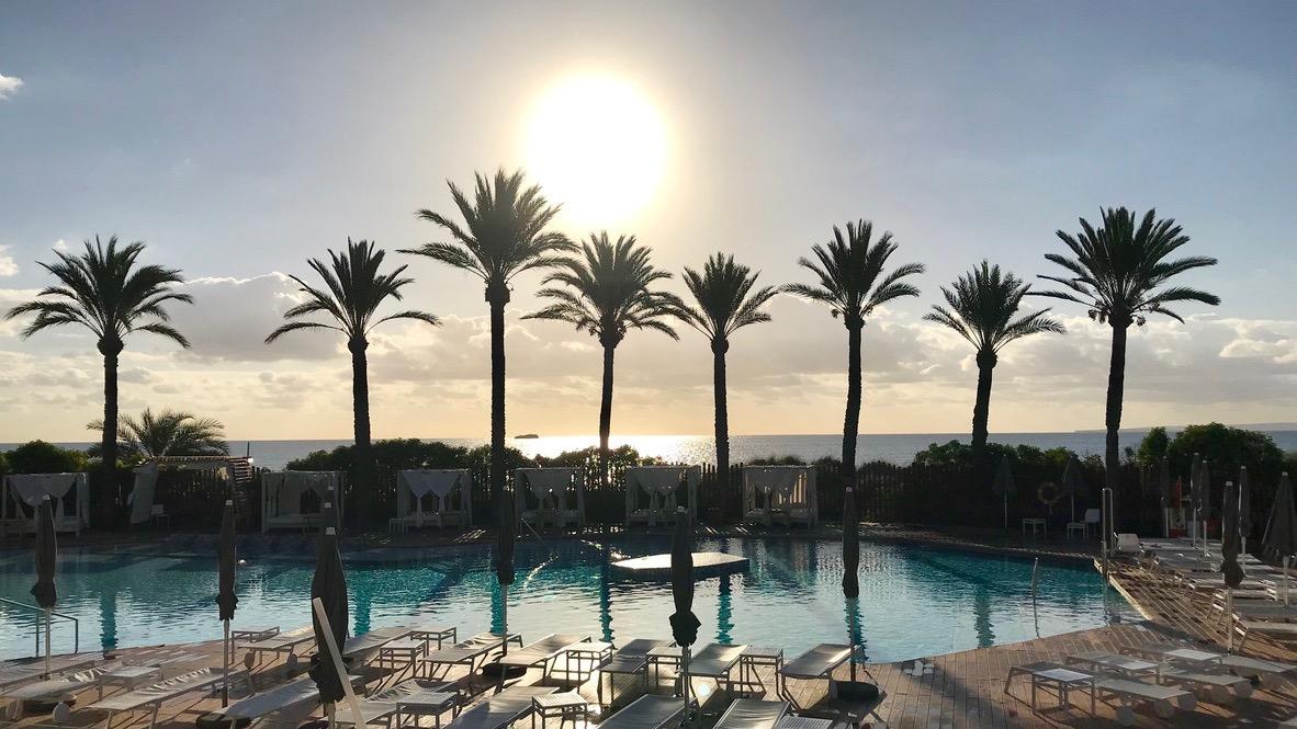 Nur einer der Pools im Hard Rock Hotel Ibiza. Weiße Liegen, Grüne Palmen und dahinter das blaue Meer. Traumhaft schön