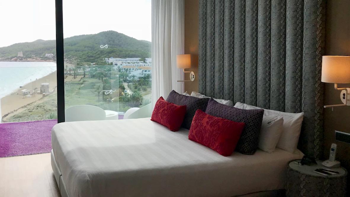 Hard Rock Hotel Ibiza Studio Suite Gold. Ein großes Bett von dem aus der ganze Ibiza Strand zu überblicken ist.