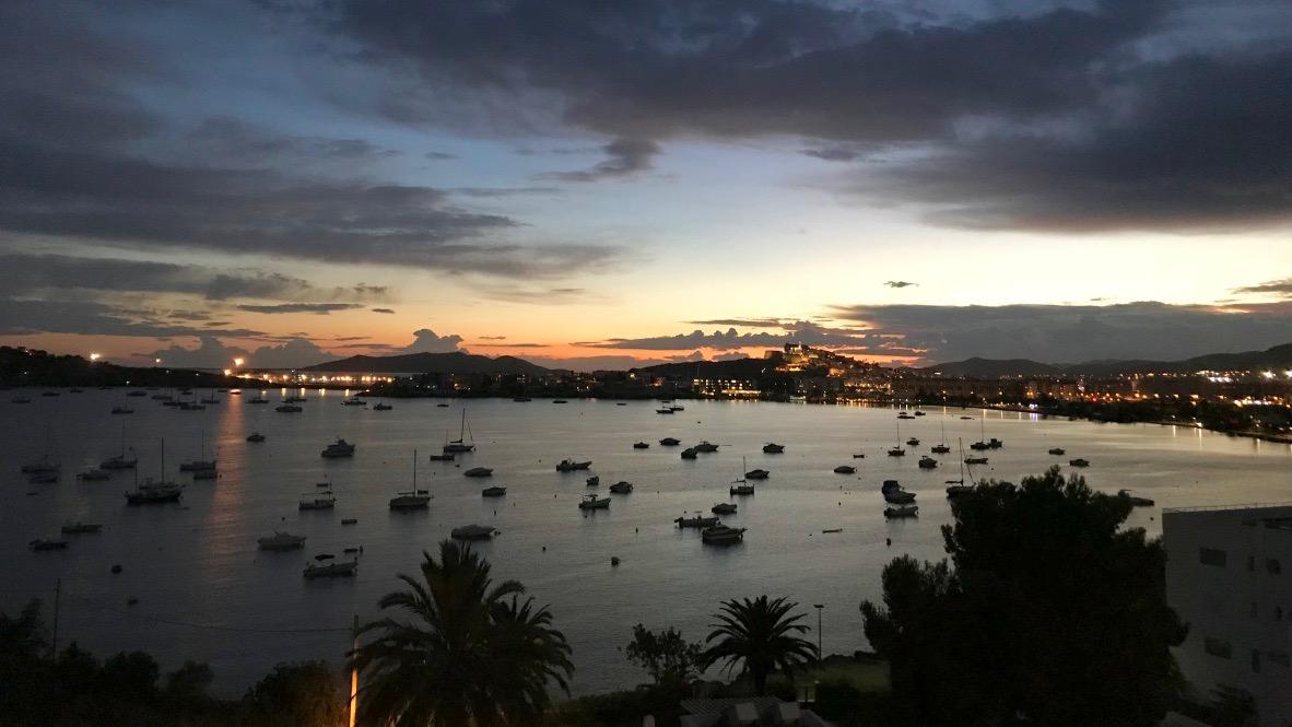 Ibiza Hafen im Sonnenuntergang. Die Altstadt leuchtet und dahinter wirft die orangegelbe Sonne ihre Licher über den Himmel.