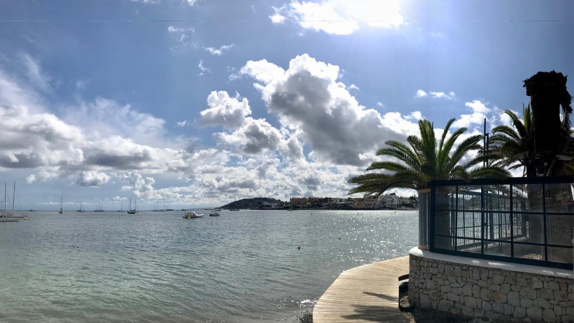 Ibiza am Strand von Talamanca, grüne Palmen, blaues Meer, kleine Yachten. Ein Holzweg führt direkt am Meer entlang und eröffnet eine Panorama-Aussicht