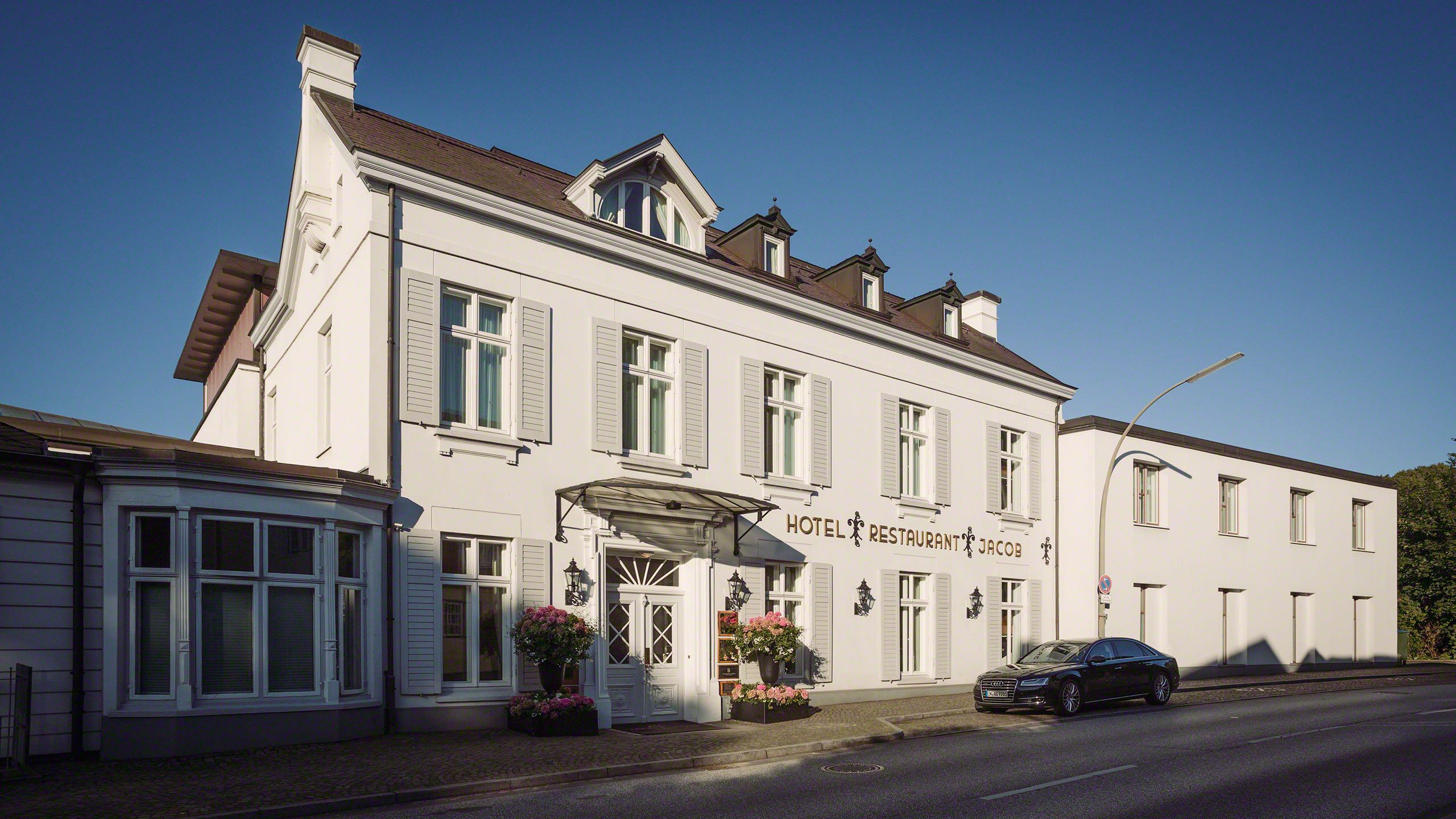 Ein hanseatisches Kaufmannshaus mit weißer Fassade an der Elbchaussee Hamburg ist das Fünf-Sterne-Hotel Louis C. Jacob. Die beste und luxuriöseste Adresse in Hamburg. Hotel Aussenfassade strahlt im Sonnenlicht