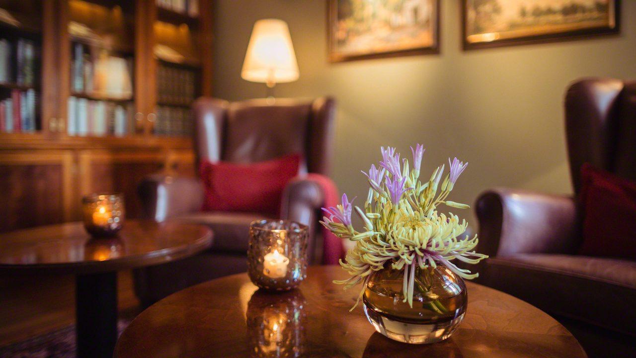 Hotel Louis C. Jacob Hamburg Bibliothek mit Bücherregal aus Holz und Glas mit unzähligen Büchern. Zwei rotbraune Ledersessel landen zum Entspannen ein. Brennende Teelichte und Lampen sorgen für ein warmes angenehmes Licht. Eine kleine Vase mit lila Blumen steht auf dem Holztisch.