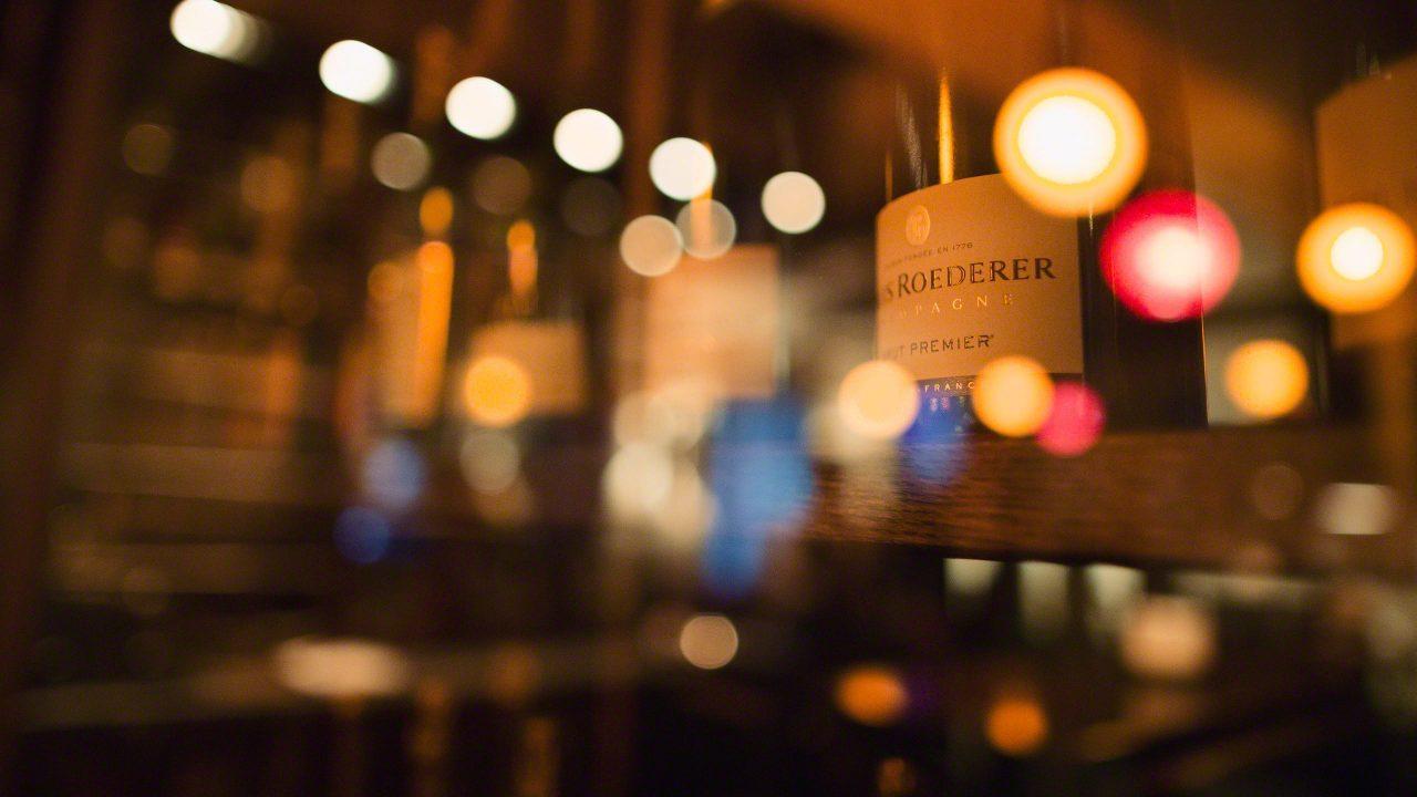 Die Jacobs Bar im nächtlichen Hotel Louis C. Jacob Hamburg mit Champagner Flasche Roederer im Schein von bunten Lichtern und Lampen.