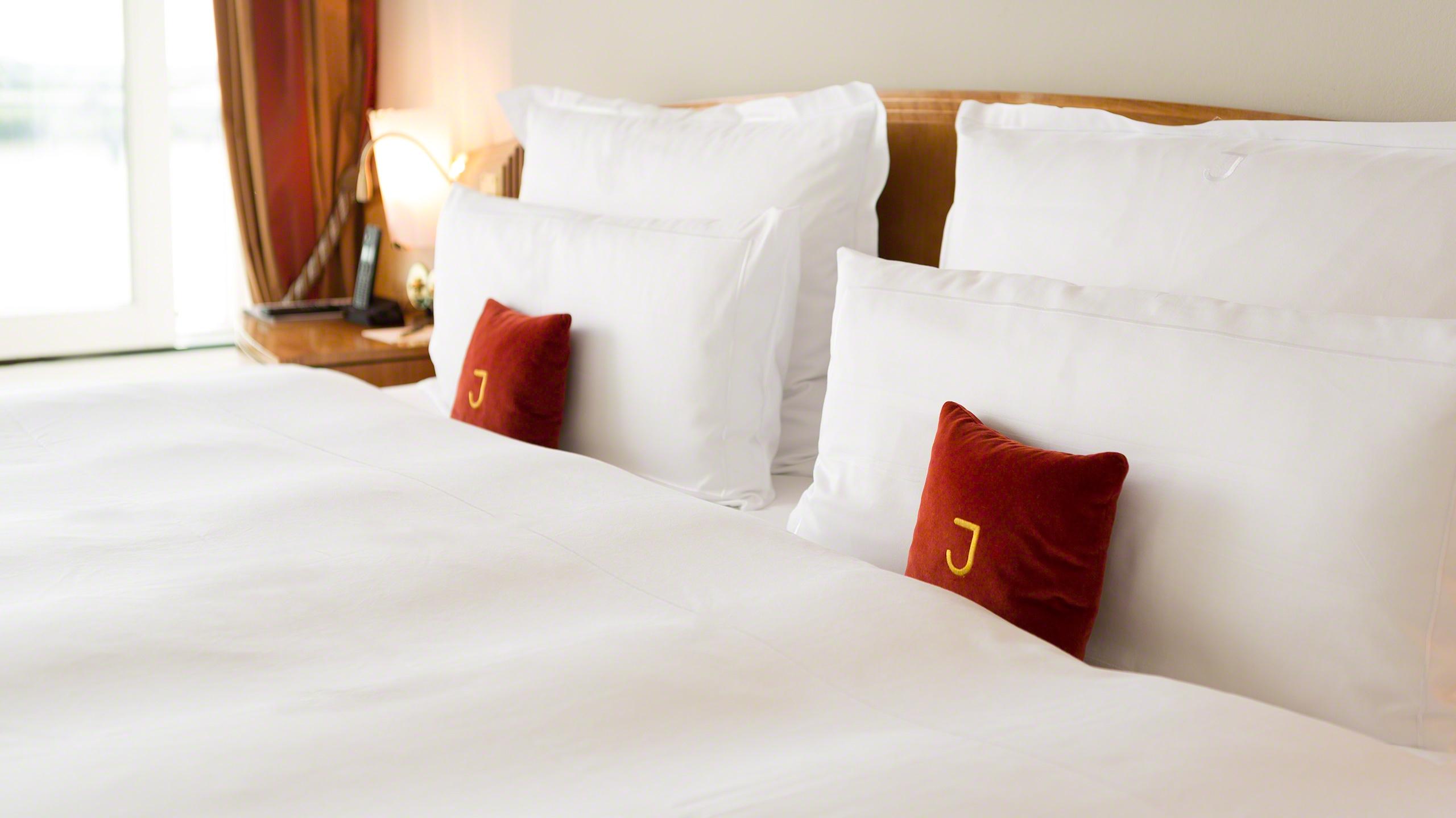 Luxus Elbsuite mit Hafen Panorama im Hotel Louis C. Jacob Hamburg. Ein weißbezogenes Doppelbett im lichtdurchfluteten Hotelzimmer. Mit Elbblick