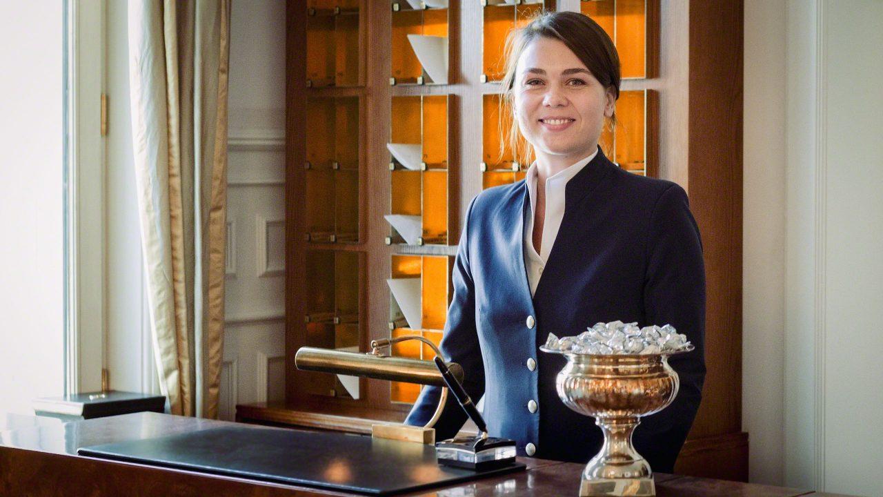 Hotel Louis C. Jacob Hamburg Empfangsdame. Freundliches Lächeln im Gesicht. Hübsche junge Frau. Tresen mit Lampe und im Hintergrund Hotelregal mit Zimmerschlüsseln.
