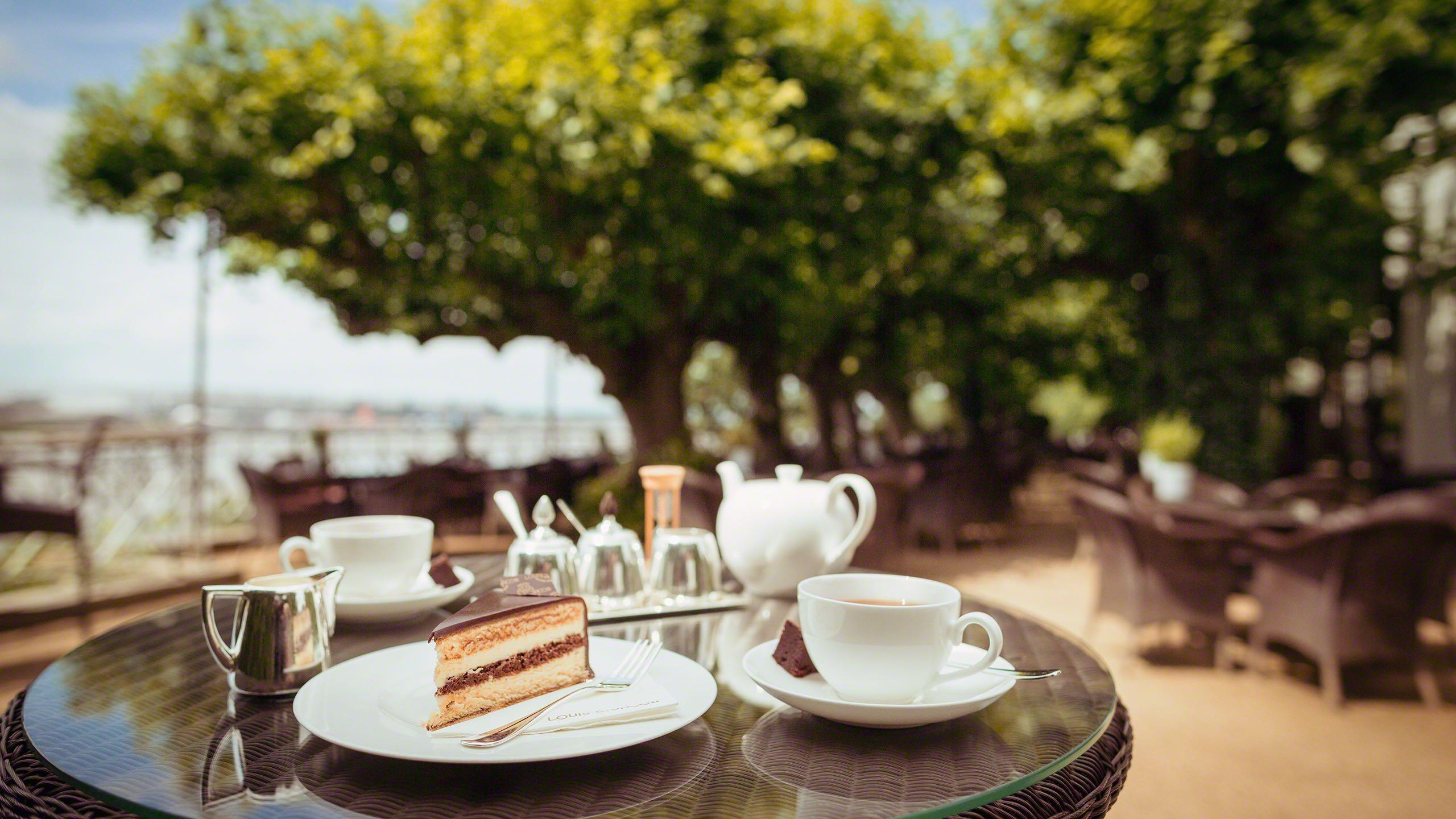 Lindenterrasse des Hotel Louis C. Jacob Hamburg. Der Tisch ist eingedeckt mit Tee und Champagnertorte mit Blick auf die grünen Bäume und die Elbe samt Hafen.