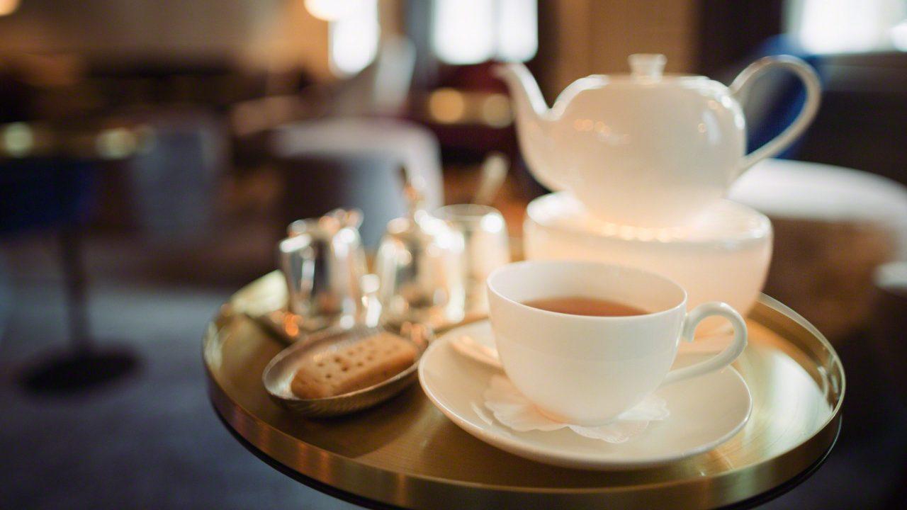 Teegenuss auf einem Tisch mit Keksen, Zucker und Milch