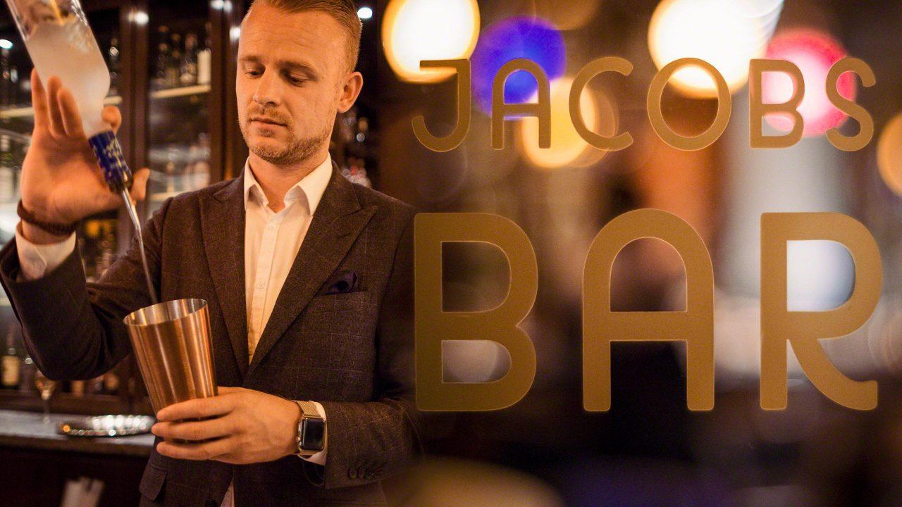 Die Jacobs Bar im nächtlichen Hotel Louis C. Jacob Hamburg mit Barmann der im Schein von bunten Lichtern und Lampen einen Cocktail mixt. Logo Jacobs Bar im Vordergrund