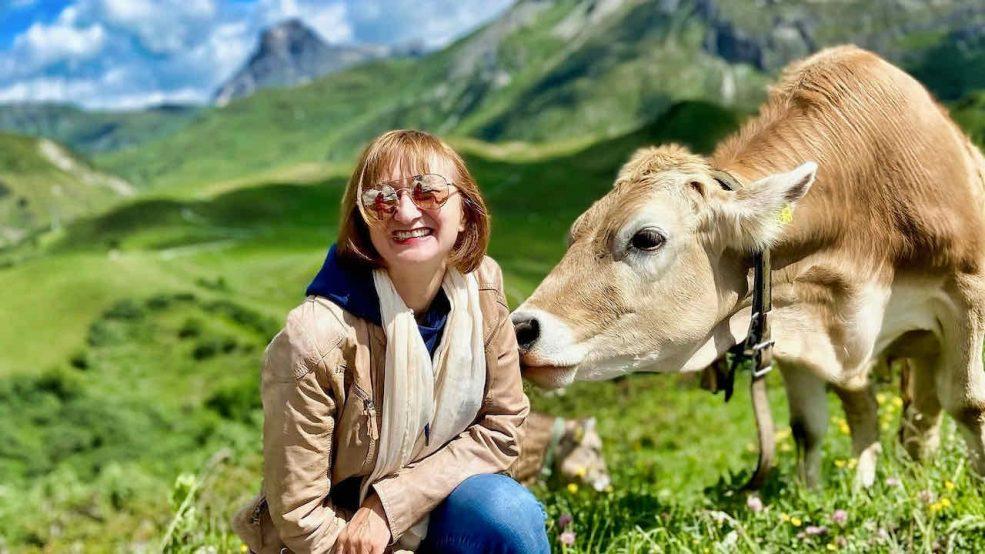 Lech am Arlberg Aurelio Chalet Luxushotel Reisetipps Reisebloggerin und Kuh im Alpenpanorama
